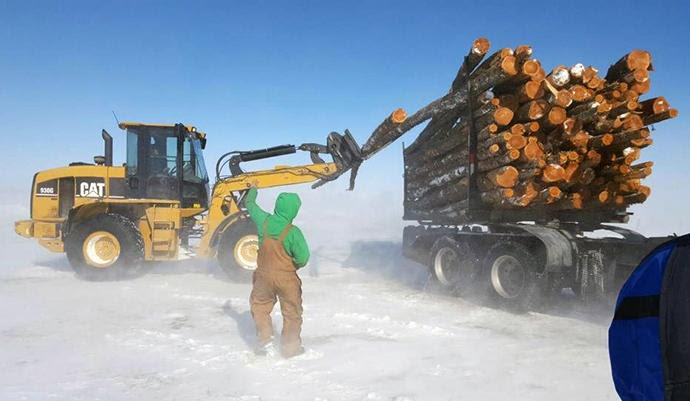 The most urgent needs are for food and firewood. Semi-trucks filled with long pine logs are delivered which volunteers then cut, split and deliver to homes in remote locations on the Blackfeet Nation. Photo courtesy of Whitefish United Methodist Church.