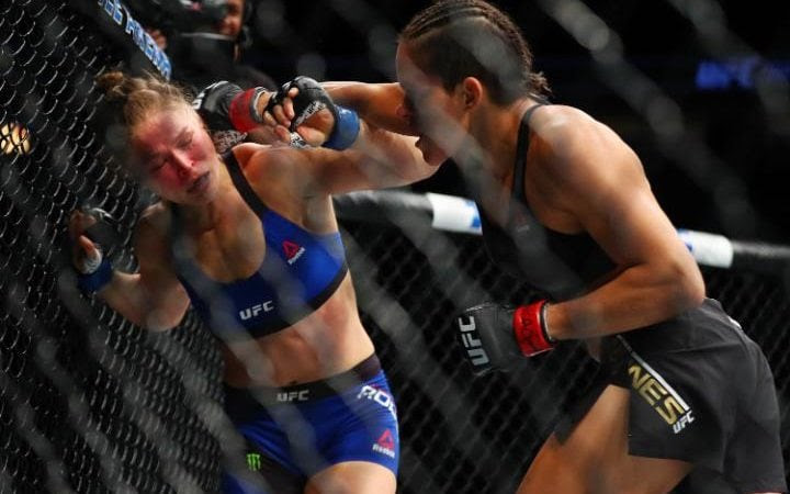 Amanda Nunes lands punches while Ronda Rousey is against the cage during UFC 207
