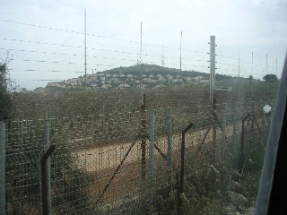 The border with Palestine showing an Israeli kibbutz on the hill.