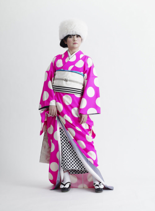 It's often hard to envision a contemporary Kimono. And yet, Takahashi Hirokohas done just that. And the result is stunning. Could we wear them? Well, that's still up for debate. Are they gorgeous? Unquestionably!  Even this kimono is not as complicated as it looks. It's a single layer (hitoe) kimono not folded under the obi (no 'tare', or extra fold visible) so it's just a regular length kimono with a Mamechiyo-esque color sense of high saturated color paired with achromatic black and white. It's worn long like a wedding kimono (or graduation) with a colorful juban—that is exactly the length of a normal juban, in fact, not a second kimono underneath.  The edge of the obi showing in back might mean it's part of a Taiko knot unfolded or the long style that maiko wear. The end result is graphic, still retaining all the kimono-ness of the kimono without compromising on style. I like it!