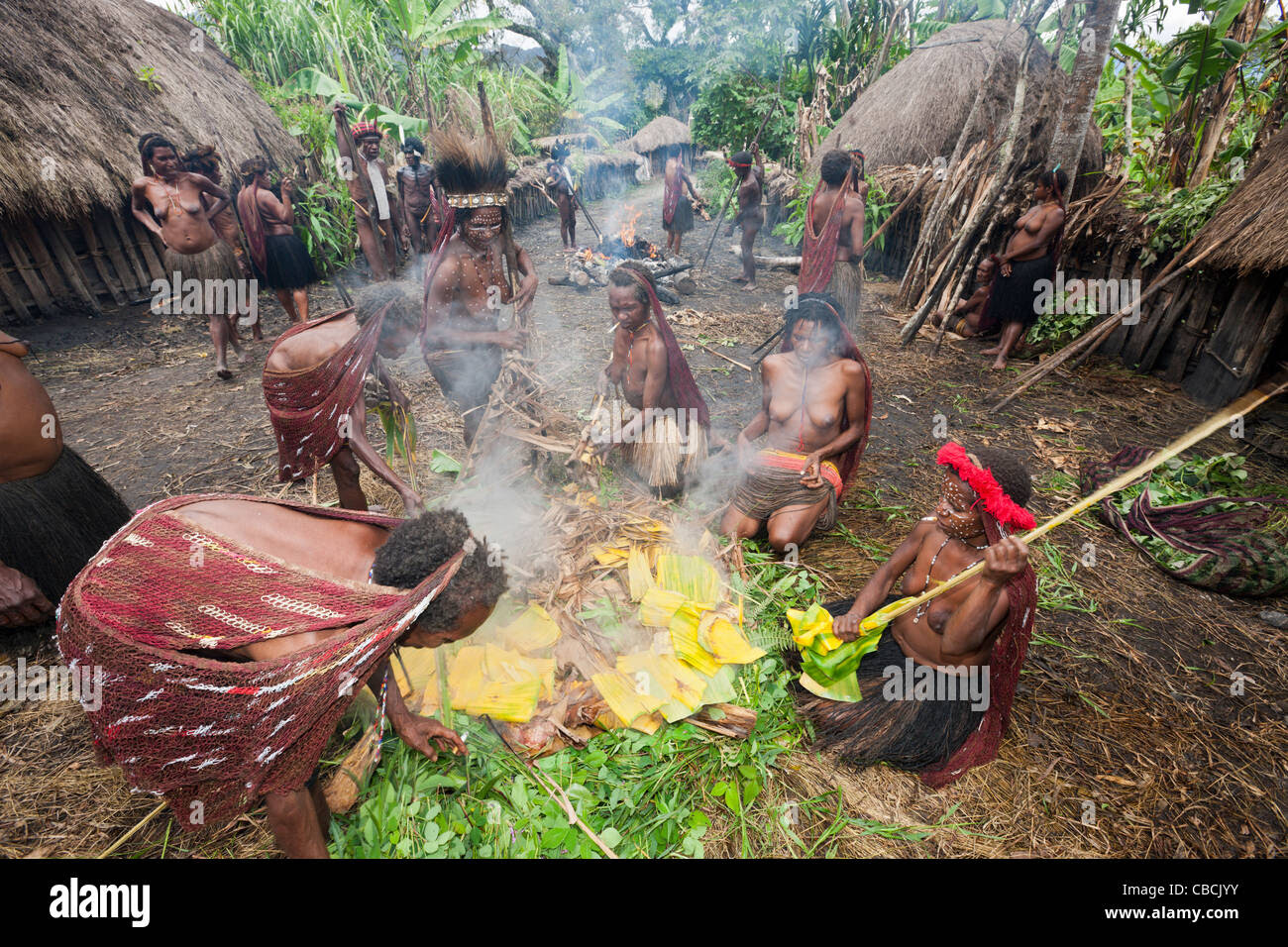 Dani Tribe preparing Earth Oven, Baliem Valley, West Papua, Indonesia Stock Photo, Royalty Free