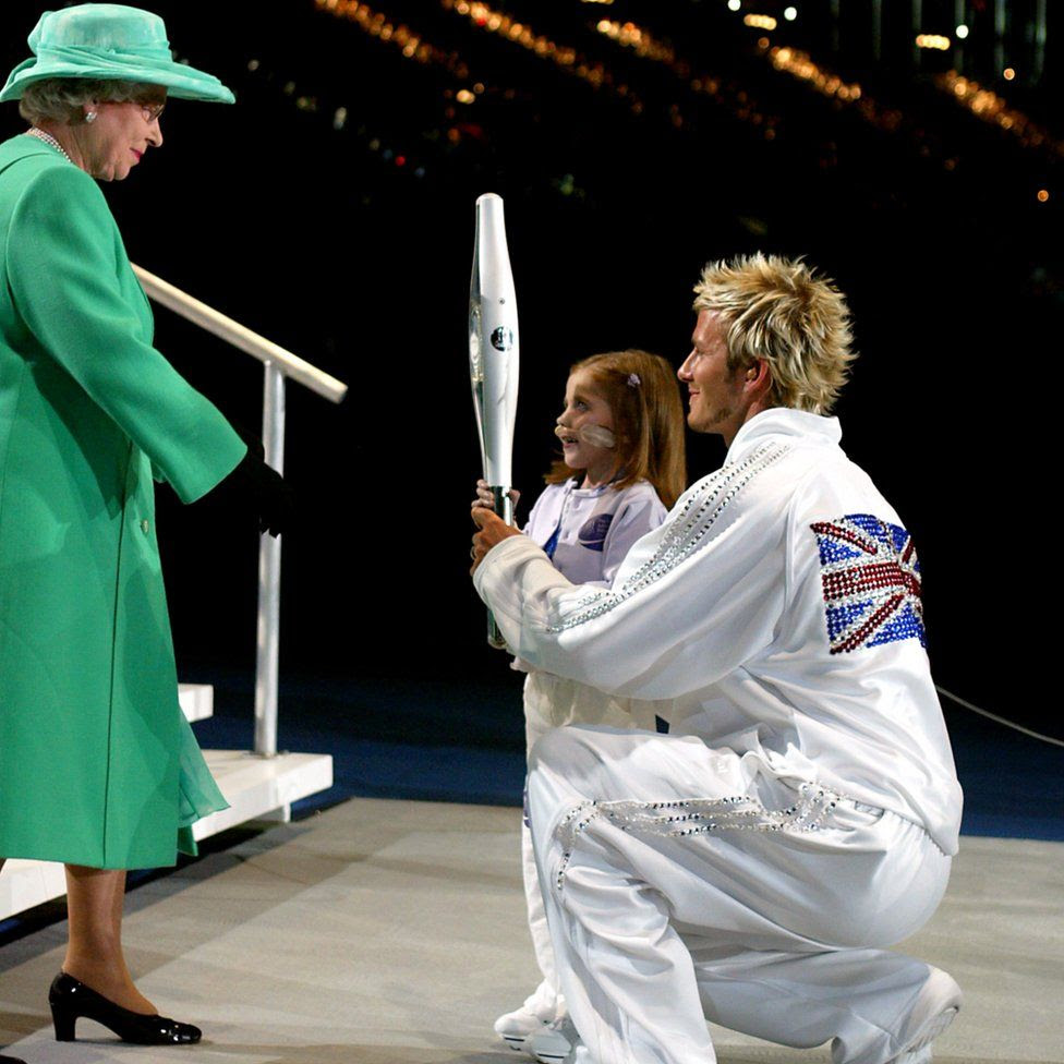 David Beckham and Kirsty Howard hand the Queens Jubilee Baton to Queen Elizabeth II after it's final leg around the city of Manchester stadium, at the opening ceremony of the Commonwealth Games.