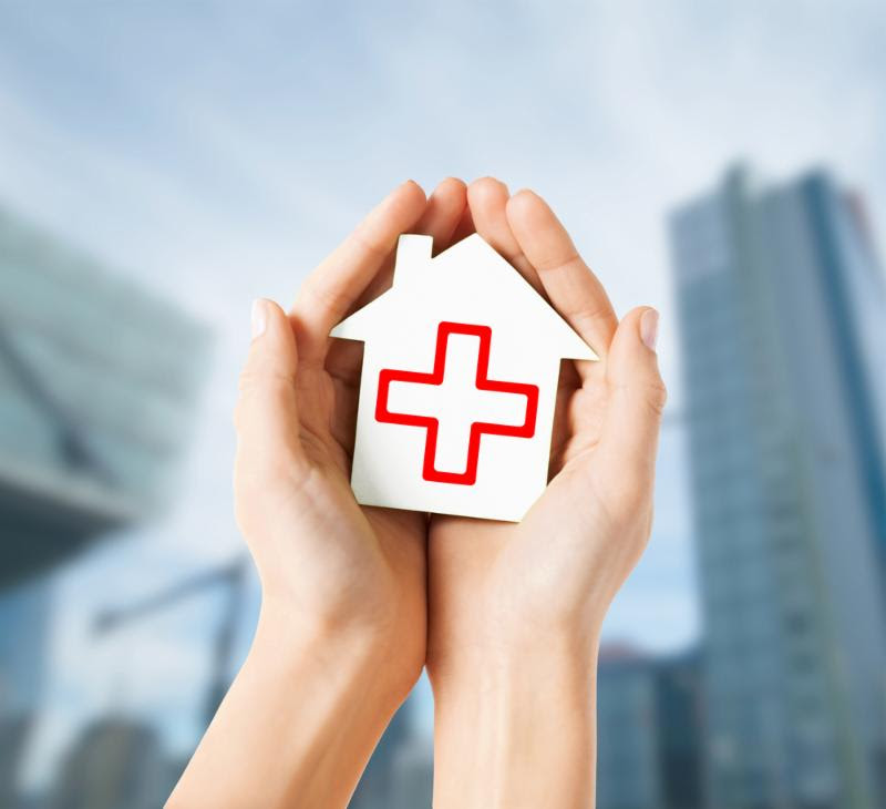 Conceptual hands holding a home with medical cross symbol painted on it.