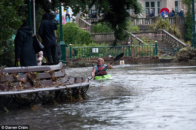A man paddles across Bournemouth gardens past the bandstand in a kayak today after a sudden downpour caused flash flooding