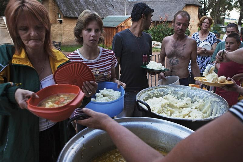 Residents of a squatter camp for poor white South Africans line up for a communal meal at Coronation Park in Krugersdorp, March 12, 2010. A shift in racial hiring practices and the recent global economic crisis means many white South Africans have fallen on hard times. Researchers now estimate some 450 000 whites, of a total white population of 4.5-million, live below the poverty line and 100,000 are struggling just to survive in places such Coronation Park, a former caravan camp currently home to more than 400 white squatters. Picture taken March 12, 2010. To match feature SAFRICA-WHITES REUTERS/Finbarr O'Reilly (SOUTH AFRICA)