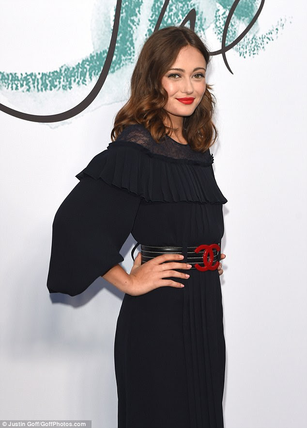 Blushing beauty: Actress Ella Purnell opted for a demure look in a black pleated maxi-dress, cinching in her tiny waist with a wide Chanel monogrammed belt
