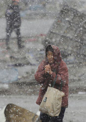 Life in quake-hit Ofunato: A woman walks by her destroyed home amid snowfall in the quake-hit city of Ofunato in Iwate Prefecture, northeastern Japan, on March 16, 2011. The area was devastated by a massive earthquake and tsunami on March 11. (Kyodo, used w/o permission)