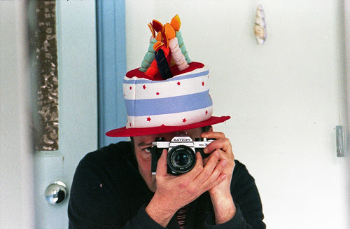 reflected self-portrait with Pentax K1000 camera and party hat (135mm lens) by pho-Tony