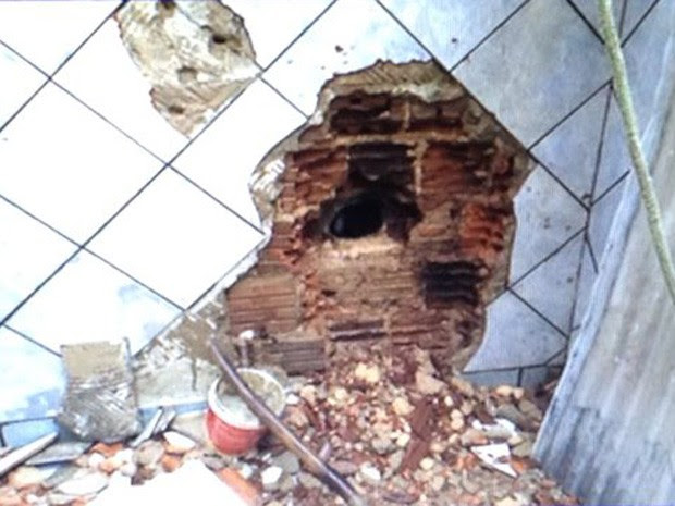 Suspeitos tentavam quebrar parede para chegar a caixa eletrônico do outro lado (Foto: Polícia Civil/Divulgação)