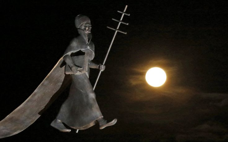 A full moon, the last of this year's supermoons, rises near a statue of Pope Leon IX in Eguisheim
