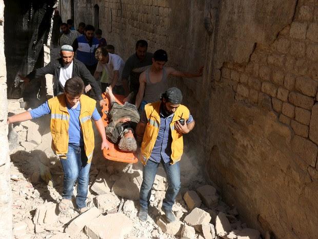 Membros da Defesa Civil síria carregam ferido após bombardeio em Alepo (Foto: Reuters/Abdalrhman Ismail)