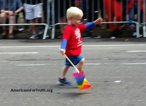 "Innocent to the Depravity that Surrounds Him: A little boy marches in New York City's 2015 homosexual ""pride"" parade holding a ""raiinbow flag."" Homosexual parenting subjects innocent children to an environment that is not only intentionally motherless or fatherless, but also one that teaches them that wrong is right."