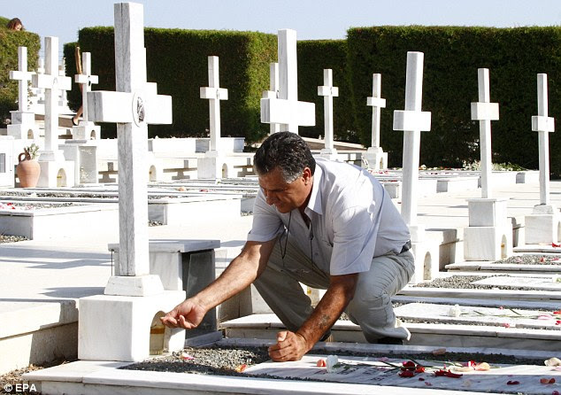 True cost: The European Court of Human Rights said the passage of time did not erase Turkey's responsibility for the invasion of Cyprus. Pictured is a man lighting a candle at the grave of a relative who died in the conflict