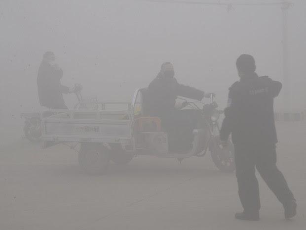Policial fala com motorista em rodovia em meio a intensa poluição em Handan, na província de Hebei, na China, nesta quinta-feira (23) (Foto: Chinatopix via AP)