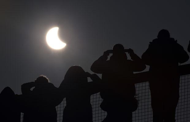 Pessoas assistem ao eclipse solar em Cornwall, na Inglaterra, nesta sexta-feira (20) (Foto: Ben Birchall/PA/AP)