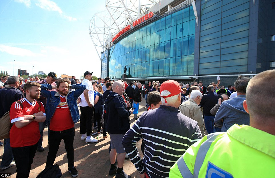 Fans await news after being evacuated from Manchester United's ground ahead of kick-off. The Premier League match was later postponed
