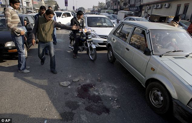 People look at blood stains on the busy Lahore road where the men were shot. Pakistani officers have said the men were likely to be robbers and both were carrying pistols
