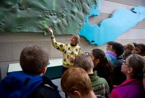 museum volunteer talks to school kids