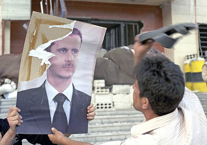 A fighter beats a poster of Syrian President Bashar al-Assad after rebel forces stormed a government position in Al-Tall, Syria, July 19, 2012.