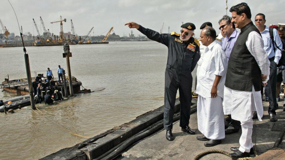El Almirante Jefe de la Armada D.K. Joshi explica la situación del submarino, del que sólo emerge una porción de la vela, al ministro de Defensa A.K. Antony (Foto: Ministerio de Defensa de India)