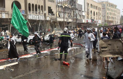 Un pélerin brandissant un drapeau passe devant des voitures détruites dans un attentat revendiqué par le groupe EI contre un pélerinage chiite à Bagdad, le 9 mai 2015 © AHMAD AL-RUBAYE AFP