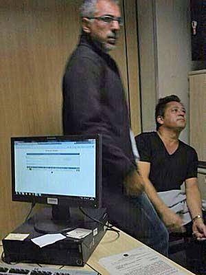 O cantor Leonardo (sentado) em sala da PF no aeroporto JK, após ter sido preso por carregar munição (Foto: Divulgação)