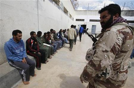 A rebel guards suspected mercenaries and forces loyal to Libyan leader Muammar Gaddafi inside a prison in Benghazi March 24, 2011. REUTERS-Suhaib Salem