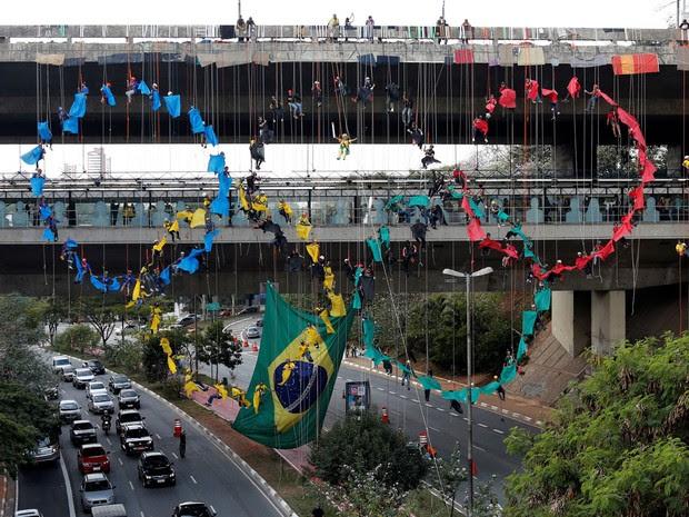 Grupo de praticantes de rapel formam os anéis olímpicos no viaduto do Metrô Sumaré, em São Paulo (Foto: Paulo Whitaker/Reuters)