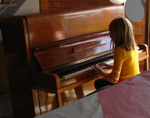 Menina improvisa ao piano abandonado