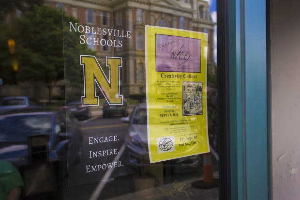 A poster for Noblesville Schools hangs in a coffee shop window of Noble Coffee and Tea Company. (Peter Balonon-Rosen/Indiana Public Broadcasting)