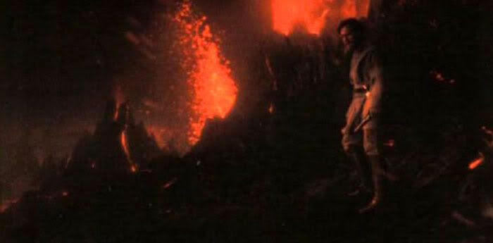 Obi-Wan picks Anakin's lightsaber up from the black sand.