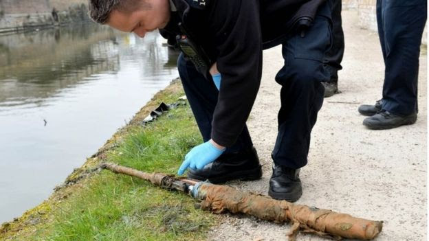 Police officers inspect a firearm on the canal bank after being removed from the canal as volunteers and staff from the Canal River Trust remove rubbish and some more bizarre objects that have been dumped into an east London canal