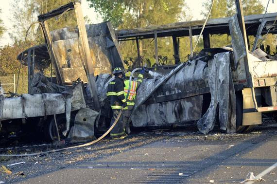 Fire-fighters douse the wreckage at the scene of a collision of a tractor-trailer and a tour bus on Interstate 5 near Highway 32 near Orland, California, April 10, 2014, in this handout courtesy of the Chico Enterprise Record. REUTERS/Dan Reidel/Chico Enterprise Record/Handout via Reuters