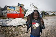 Dickenson Prudhomme, 6, walks through the Marassa 14 tent camp after the brunt of Tropical Storm Isaac collapsed his family's tent in Port-au-Prince, Haiti August 25, 2012. The storm dumped torrential rains on Haiti and flattened tent camps housing survivors of the a devastating earthquake, then began an assault on eastern Cuba.  REUTERS/Benjamin Rusnak/Food for the Poor/Handout  (HAITI - Tags: DISASTER ENVIRONMENT) NO SALES. NO ARCHIVES. FOR EDITORIAL USE ONLY. NOT FOR SALE FOR MARKETING OR ADVERTISING CAMPAIGNS. THIS IMAGE HAS BEEN SUPPLIED BY A THIRD PARTY. IT IS DISTRIBUTED, EXACTLY AS RECEIVED BY REUTERS, AS A SERVICE TO CLIENTS