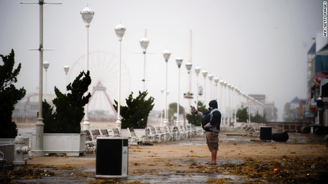 A man takes a picture of the storm with his phone from the boardwalk in Ocean City, Maryland, on Monday.