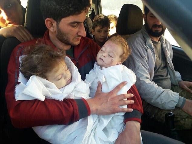 Agonia: o pai sírio Abdul Hamid al-Yousef foi retratado embalando os corpos de seus gêmeos mortos depois que eles foram mortos no ataque químico em Khan Sheikhoun, na província central rebelde de Idlib, na Síria
