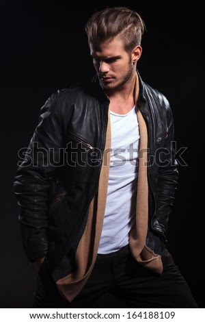 side view of a fashion man in leather jacket is looking to his back on dark background - stock photo