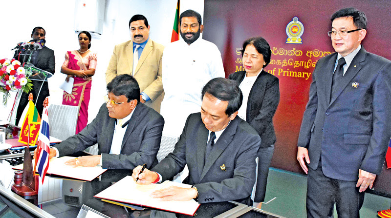 Primary Industries Ministry Secretary Eng. Bandula Wickremaarchchi and Bank for Agriculture and Agricultural Cooperatives of Thailand Senior Executive Vice President Apirom Sukprasert signing the MoU while Primary Industries Minister Daya Gamage and Thai Ambassador to Sri Lanka Chulamanee Chartsuwan look on.