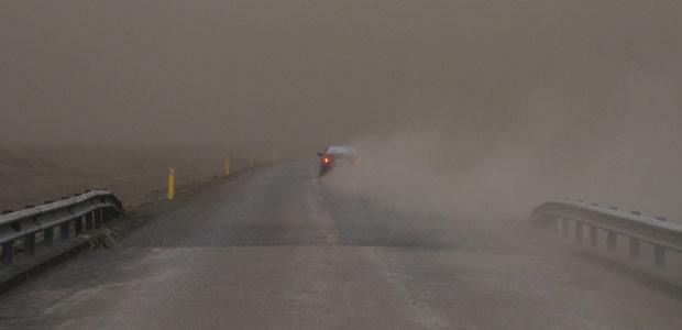 Carro passa por rodovia imerso na escuridão devido à precipitação de cinzas do vulcão (Foto: Ingolfur Juliusson/Reuters)
