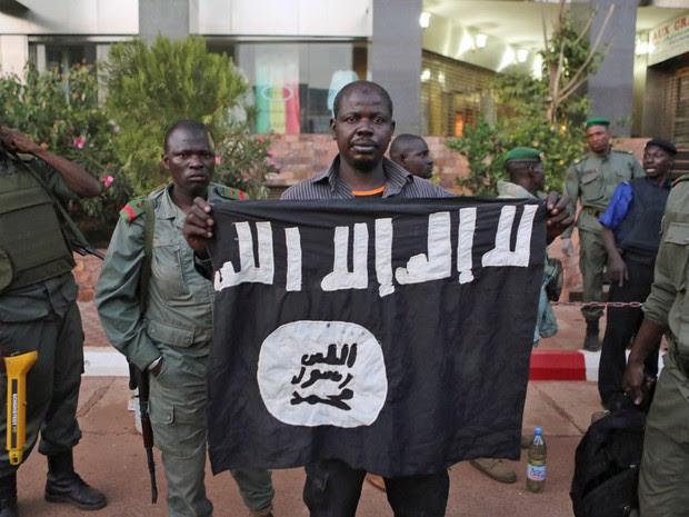 Policiais exibem bandeira que dizem ser de terroristas que invadiram hotel no Mali (Foto: Joe Penney/Reuters)
