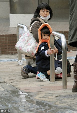 A mother and child crouch on a street in Tokyo while an earthquake hits Friday, March 11, 2011.
