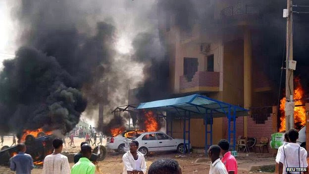 Cars burn in front of a building during protests over fuel subsidy cuts in Khartoum September 25, 2013.