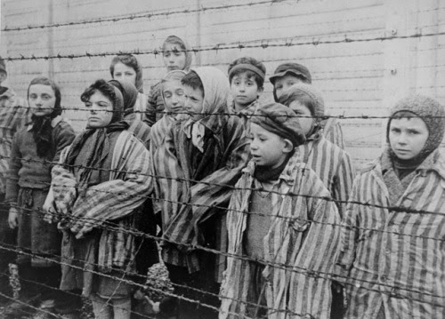 Child survivors of Auschwitz, wearing adult-size prisoner jackets, stand behind a barbed wire fence. Among those pictured are Tomasz Szwarz; Alicja Gruenbaum; Solomon Rozalin; Gita Sztrauss; Wiera Sadler; Marta Wiess; Boro Eksztein; Josef Rozenwaser; Rafael Szlezinger; Gabriel Nejman; Gugiel Appelbaum; Mark Berkowitz (a twin); Pesa Balter; Rut Muszkies (later Webber); Miriam Friedman; and twins Miriam Mozes and Eva Mozes wearing knitted hats. 1945, Auschwitz, [Upper Silesia] Poland Credit: Belarusian State Archive of Documentary Film and Photography