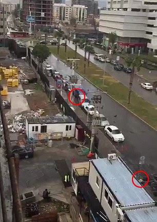 Further footage then shows what appears to be a second officer (circled bottom) being shot by an attacker (circled top)
