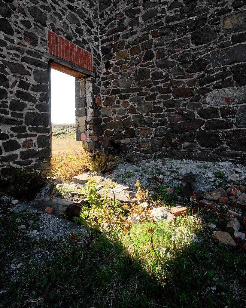 Light shining in through an old rock doorway.