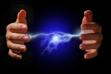 Hands and electric discharge over black background.