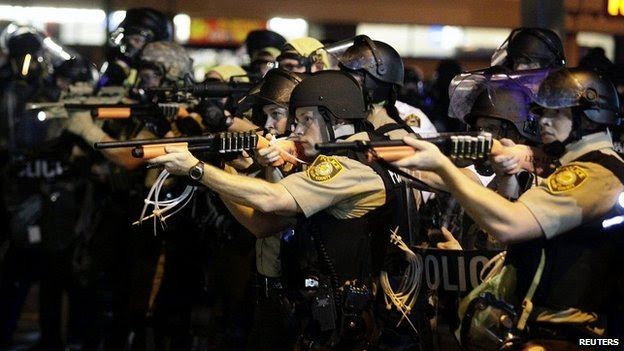 Police officers point their weapons at demonstrators protesting against the shooting death of Michael Brown in Ferguson, Missouri - 18 August 2014