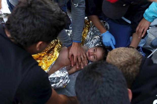 Médicos e paramédicos tentam reanimar criança após naufrágio de barco na costa da ilha de Lesbos nesta quarta-feira (28) (Foto: Giorgos Moutafis/Reuters)