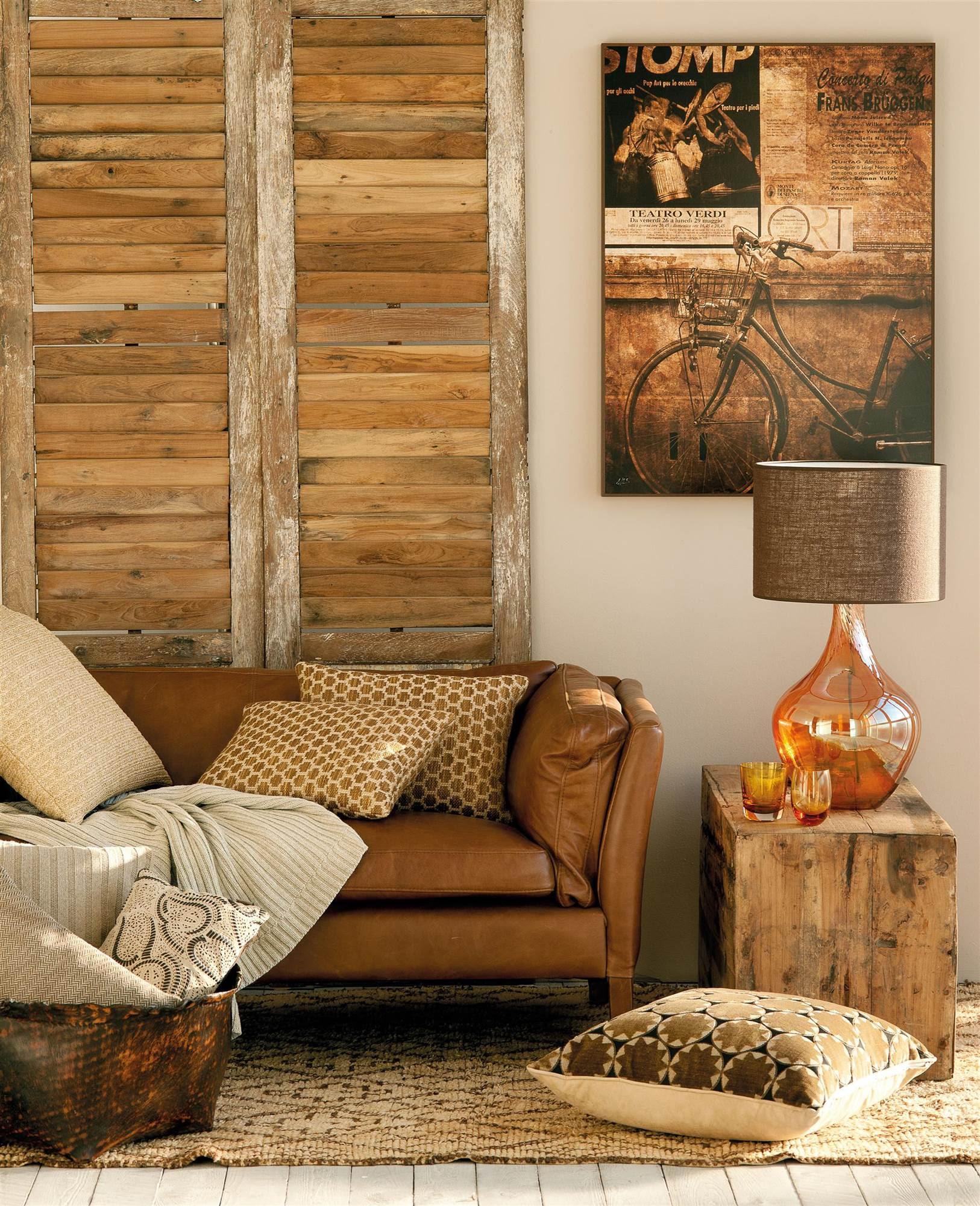 00353809. Salón en tonos marrones con sofá de cuero, puertas antiguas y detalles en cuero_00353809