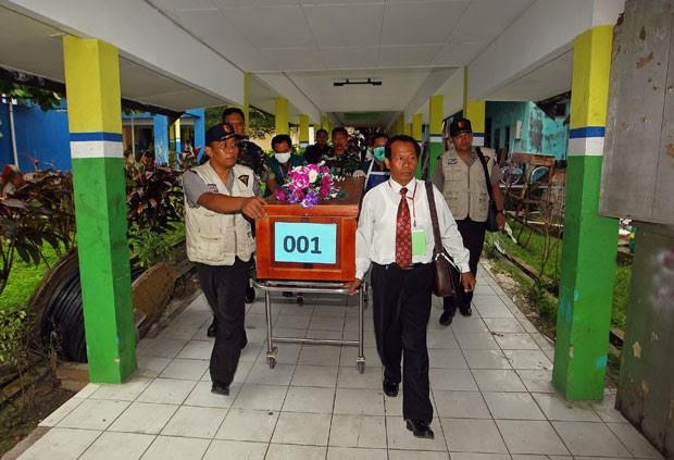 Equipes carregam caixão com corpo de vítima da queda do avião da AirAsia nesta quarta-feira (31) em um hospital de Pangkalan Bun (Foto: AFP)